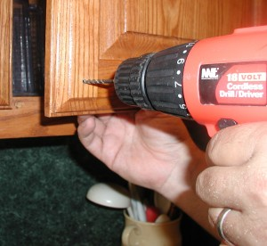 drilling for hole in cabinet